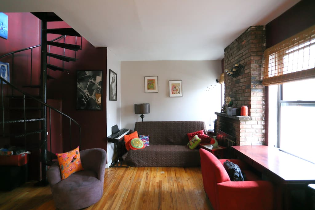 Living room downstairs with a bed to hosts 2 people