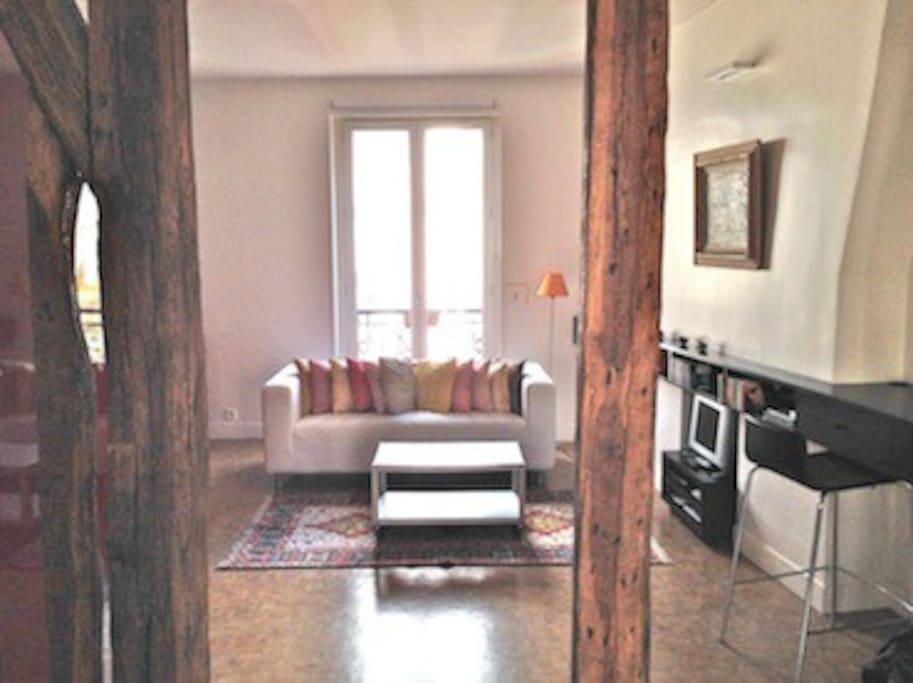 La pièce principale est divisée en deux (séjour d'un côté, cuisine/salle à manger de l'autre) ; les anciennes poutres ont été mises en valeur.