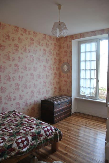 Une chambre avec un lit deux places, côte rue, doubles vitrages.