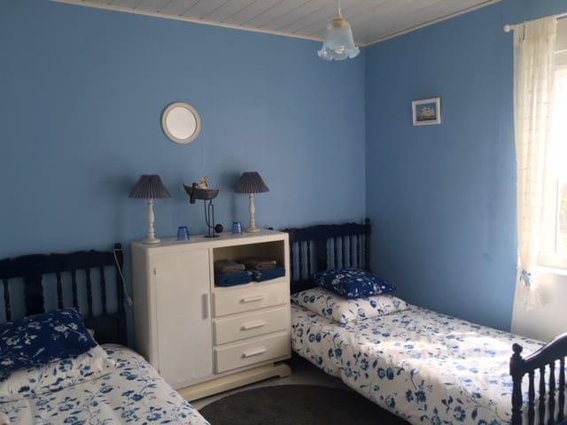 Nuances de bleues pour cette chambre au mobilier vintage. Soleil du matin sur les draps fleuris