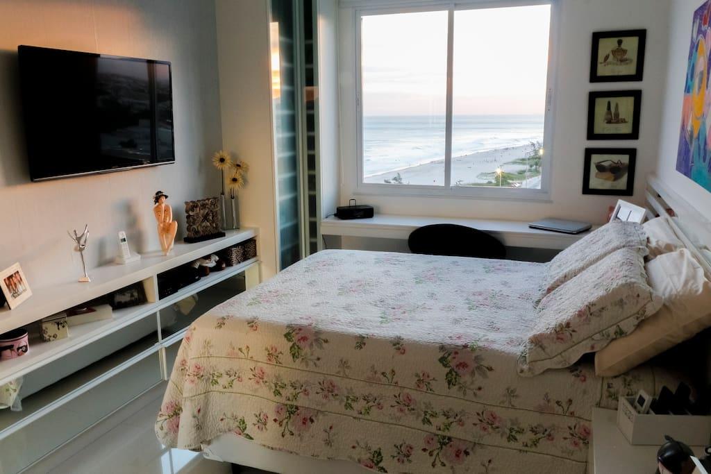 Quarto com cama de casal e vista para o mar.