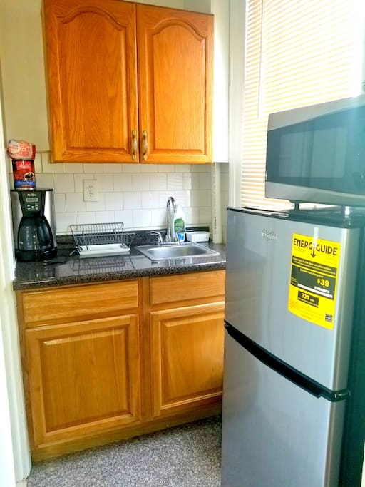 Kitchenette with Refrigerator, Microwave and Coffee Machine.