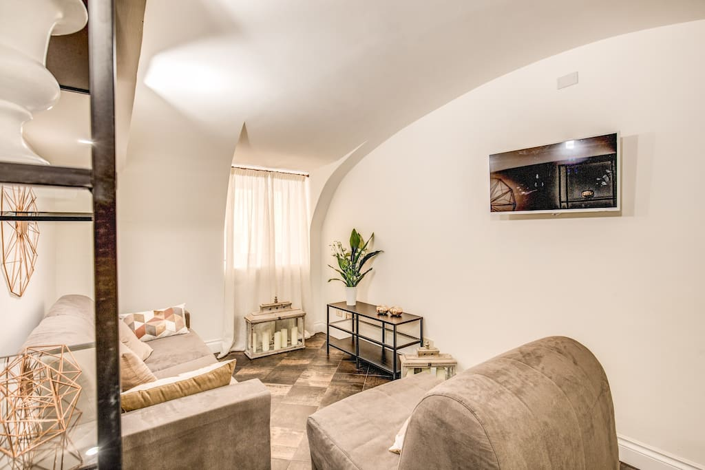 Living room with 2 sofa beds (1 double and 1 single), 1 folding table, TV and air conditioning