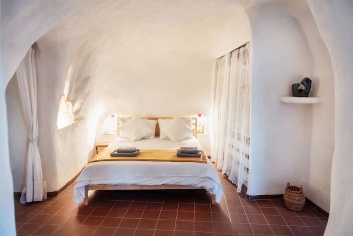 The white bedroom in our cave house rental has kingsize bed and en-suit shower room.