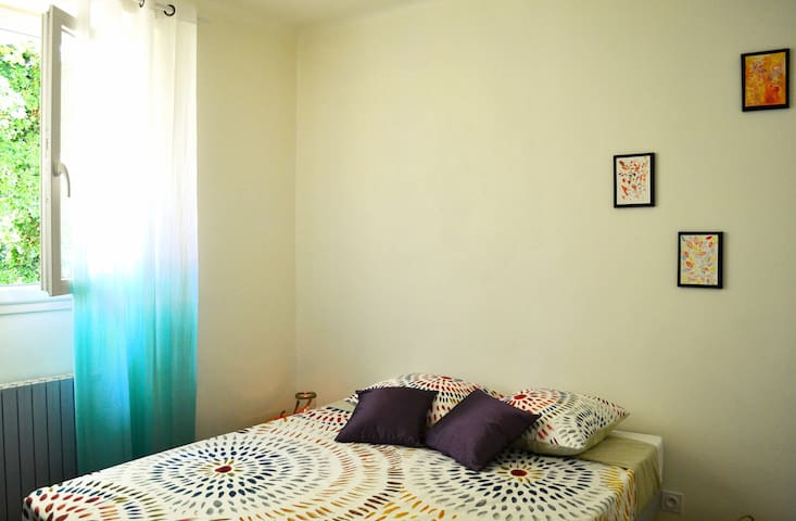 Grand lit double paré de teintes solaires et coussins moelleux vous réservent un accueil douillet à la lueur du soleil couchant.