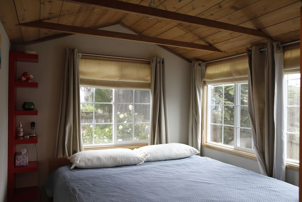 Rustic petite bedroom with king-size bed overlooking the yard