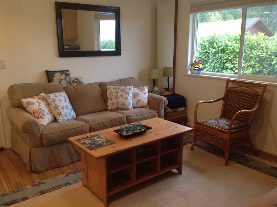 Relaxing sofa in living room with maps and guidebooks provided.