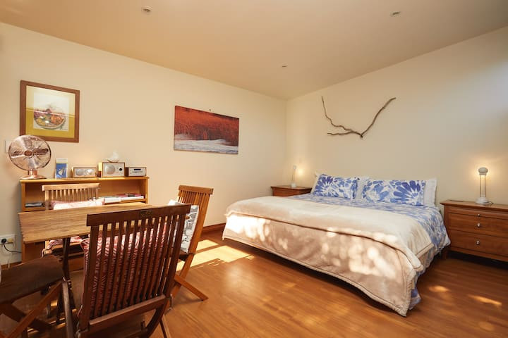 Super king bed in main room, dual purpose with a dining table and sliding door out to deck