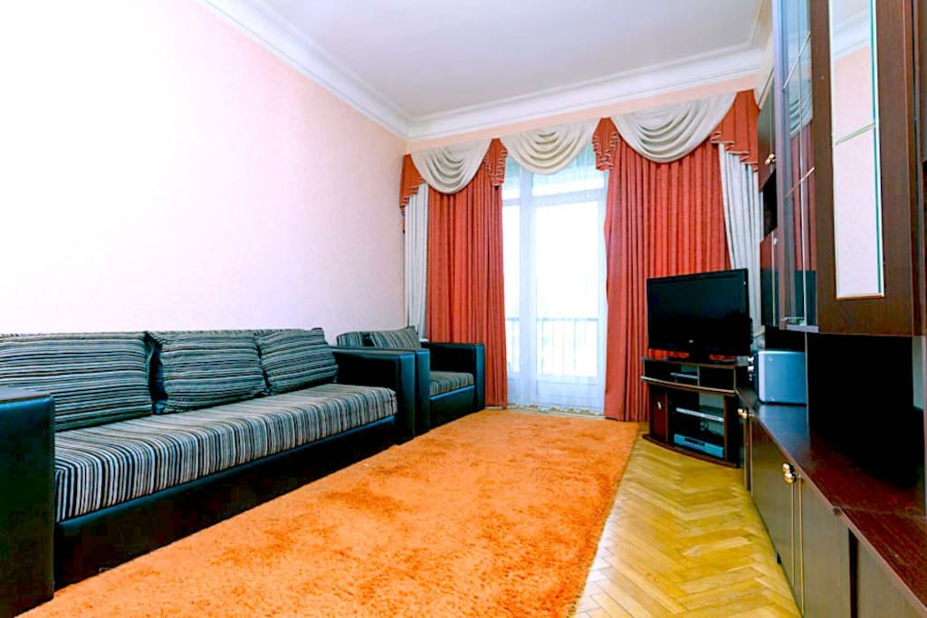 Spacious living room with access to the balcony, with a panoramic view of Kreschatik Street and Independence Square, with a sofa bed, an armchair, air conditioning and spacious wardrobes for clothes and small things.