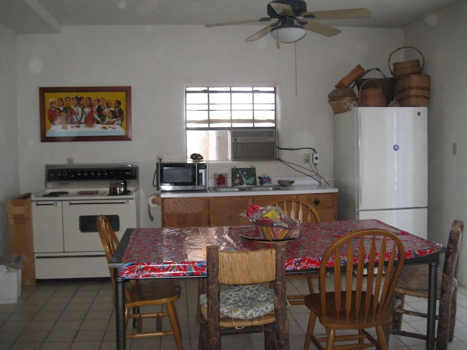The kitchen and living is an open floor plan, Electric stove, microwave, toaster, coffee maker, tea kettle, refrigerator.