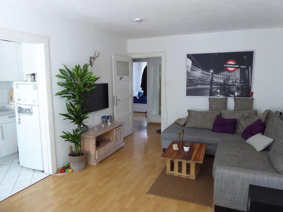 Wohnzimmer mit großer Couch, Fernseher, Küchentisch und Durchgang zur Küche