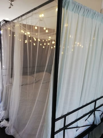 Romantic bed with light curtains and fairy lights