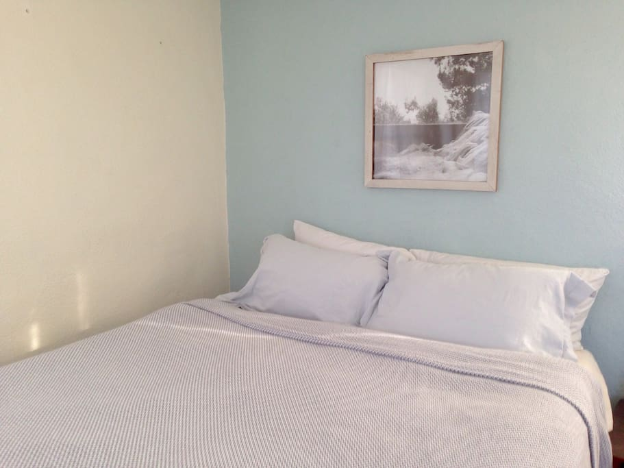 The second bedroom with comfortable queen sized bed with nice natural light from three windows