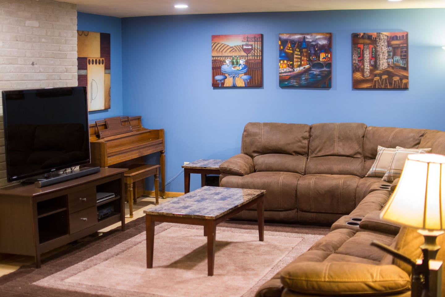"""Living area with 55"""" TV and comfy sectional couch with 6 recliners"""