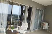 Balcony with a view of the complex swimming pool and the beautiful Sandton drive. The sliding door on the right is installed with Blockout curtains.