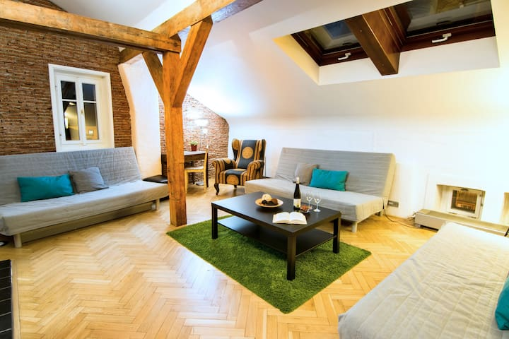 A spacious living room with an original parquet floor. Equipped with three folding sofas, armchair, television and fan