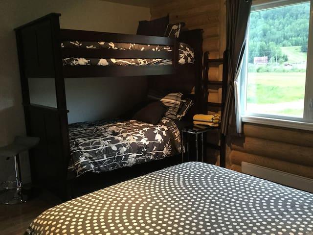 Deuxième chambre avec un lit queen  et deux lits superposés simple
