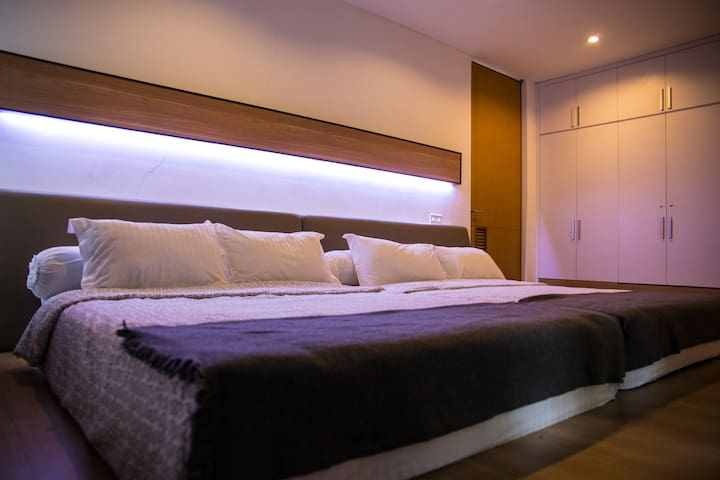 """The Master Bedroom with a """"Family Bed"""" (two 160x200 size beds) that comfortably fits 4 adults or 2 adults and 2 children.  The Master Bedroom has en-suite bathroom and is equipped with built-in vanity table, luggage table and wardrobe."""
