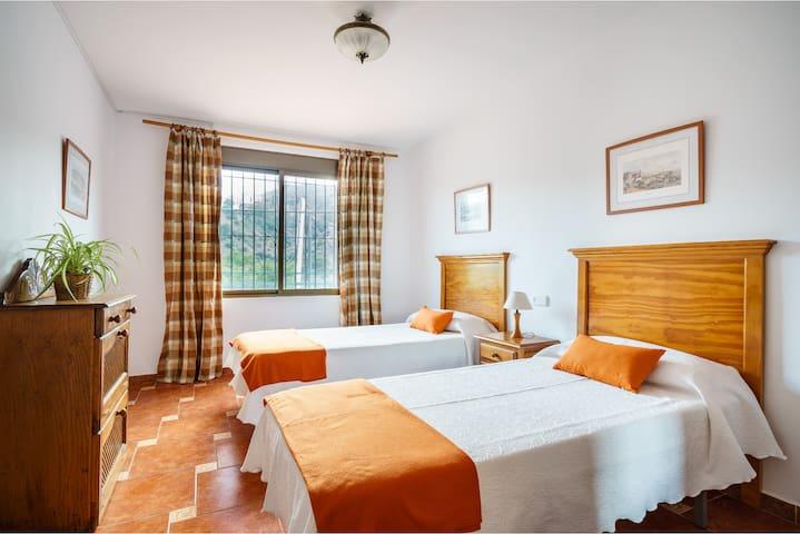 Dormitorio con 2 camas individuales. Se puede añadir una cama extra para otra persona. La ventana da a la parte trasera de la terraza de la casa.