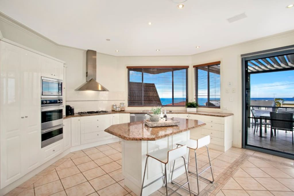 Huge open plan kitchen with sea views adjacent to a large dining area and the balcony
