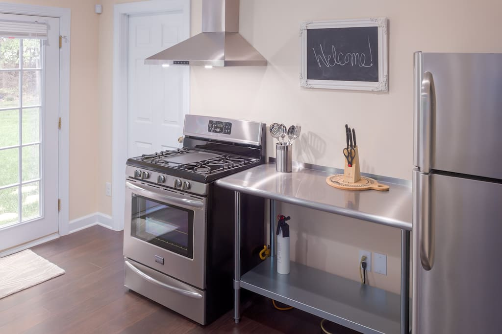 Full sized refrigerator, gas range and hood, and stainless steel work table.