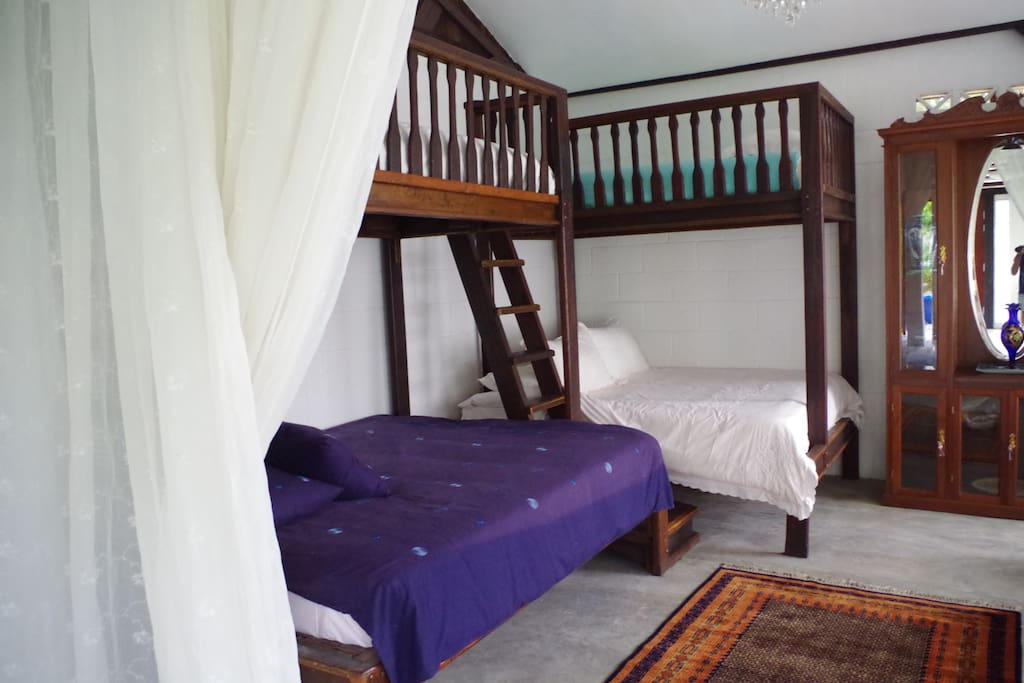 Same floor as the living area, 2 custom made bunk beds with 2 single sized beds on top, 2 queen sized bed below.