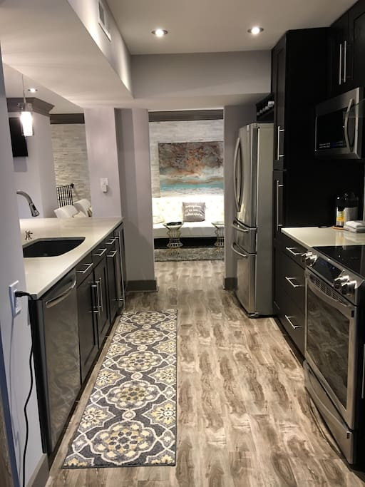 The spacious kitchen with extra large island with beverage cooler, water tower, induction range with other luxury appliances to explore while preparing or not preparing a meal.