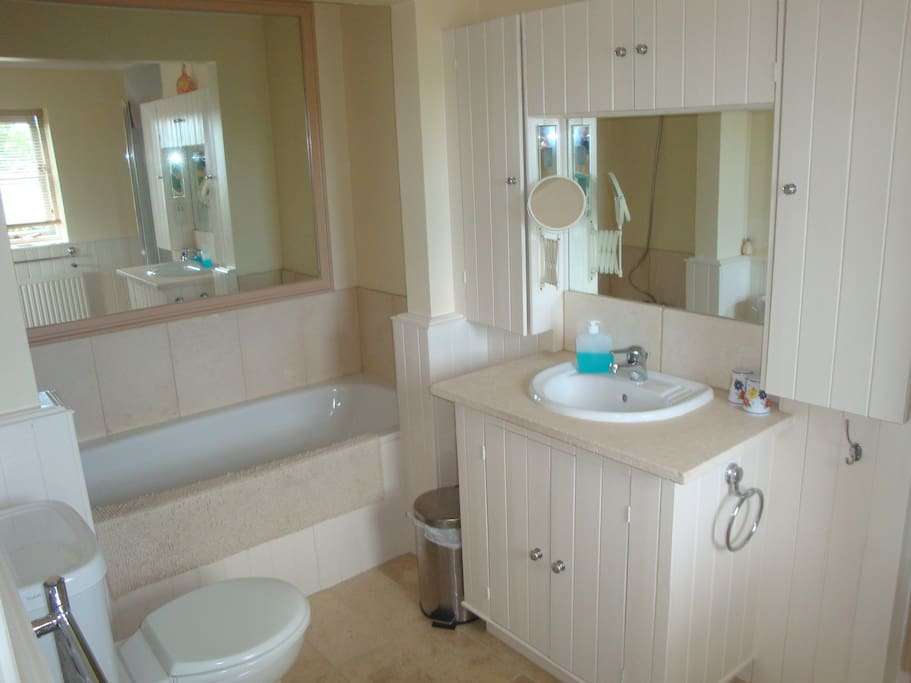 Ensuite bathroom - the bath is slow running but worth the wait. Large shower out of view to the right. Bright lighting around the mirror. Electric shaving point.