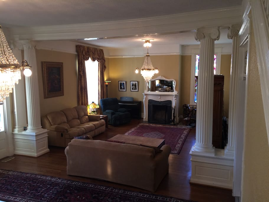 "Family room with 55"" HD TV, stained glass window, working fireplace, antique chandeliers and queen sofa bed."