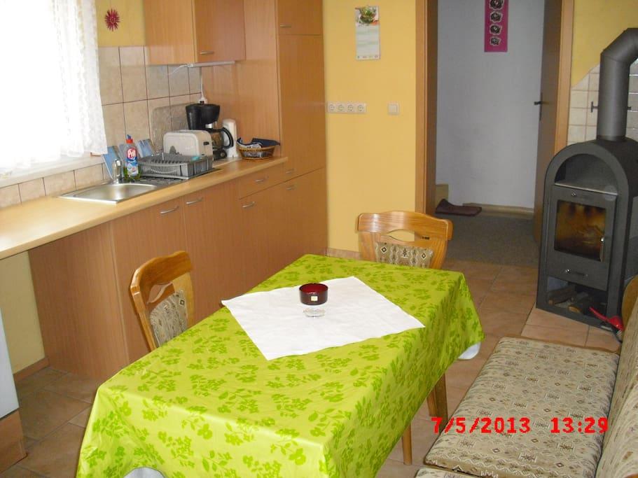 Die Küche mit Kaminofen und Sitzplätzen