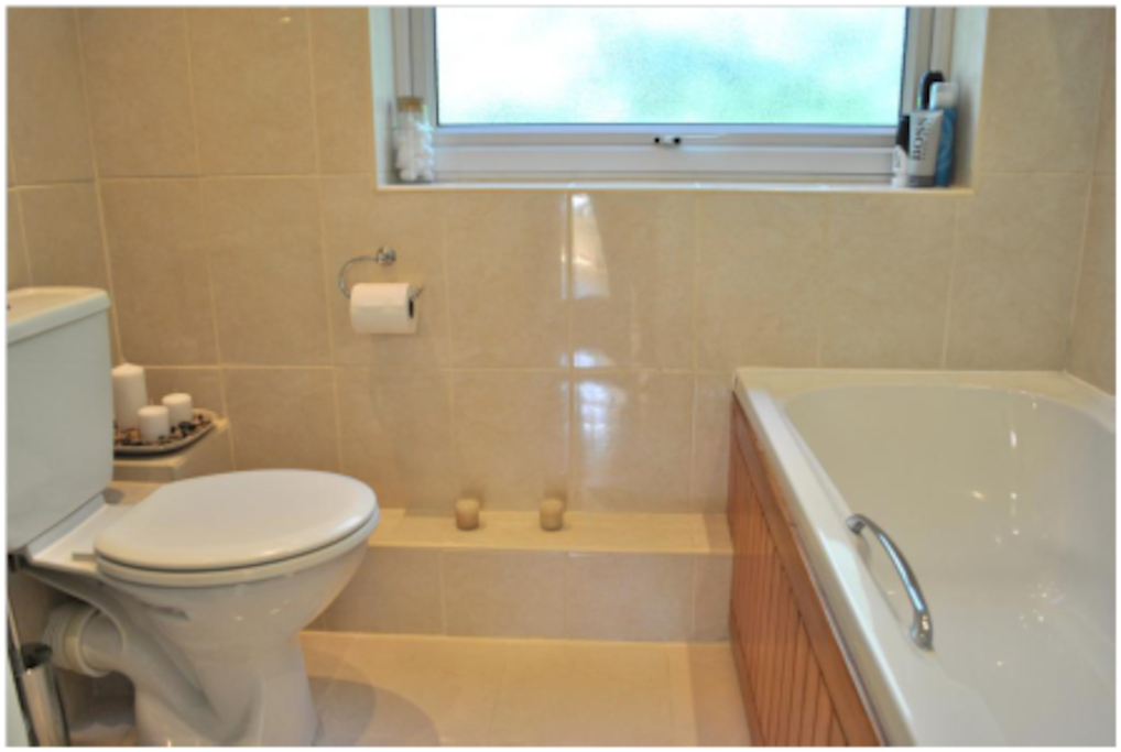 bathroom with tub and electric shower