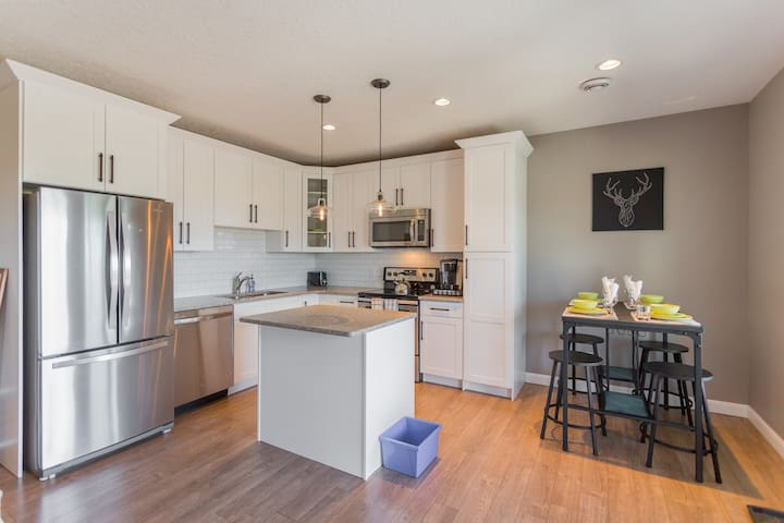 Quartz countertops & stylish lighting in fully stocked kitchen.