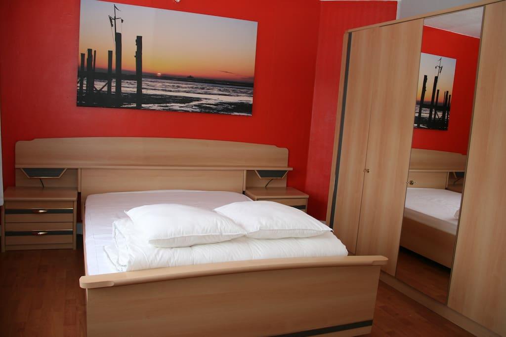 Notre chambre rouge avec un lit double.