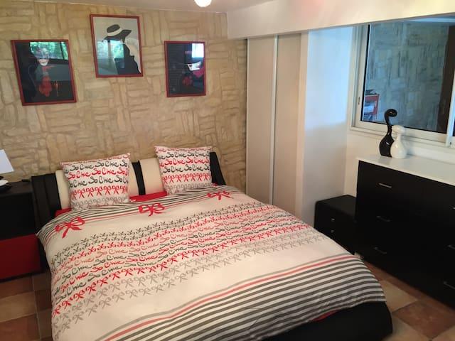 Chambre avec grand lit double, grand miroir, commode, placards, bureau et sèche serviette