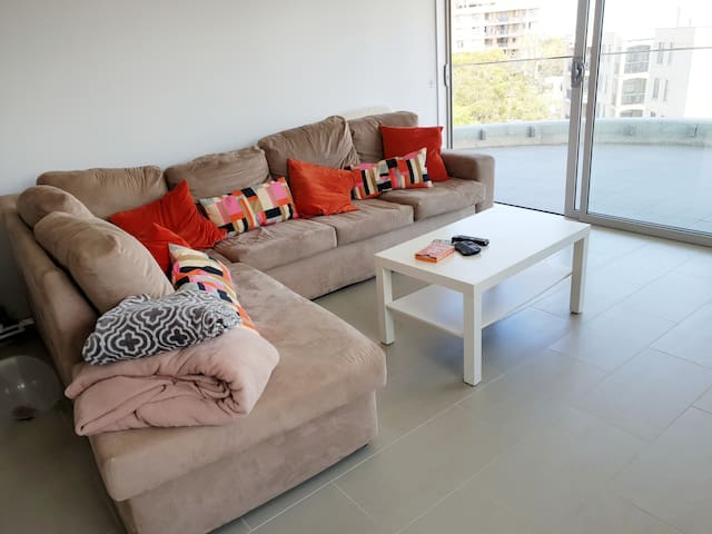 Couch leading to a spacious balcony