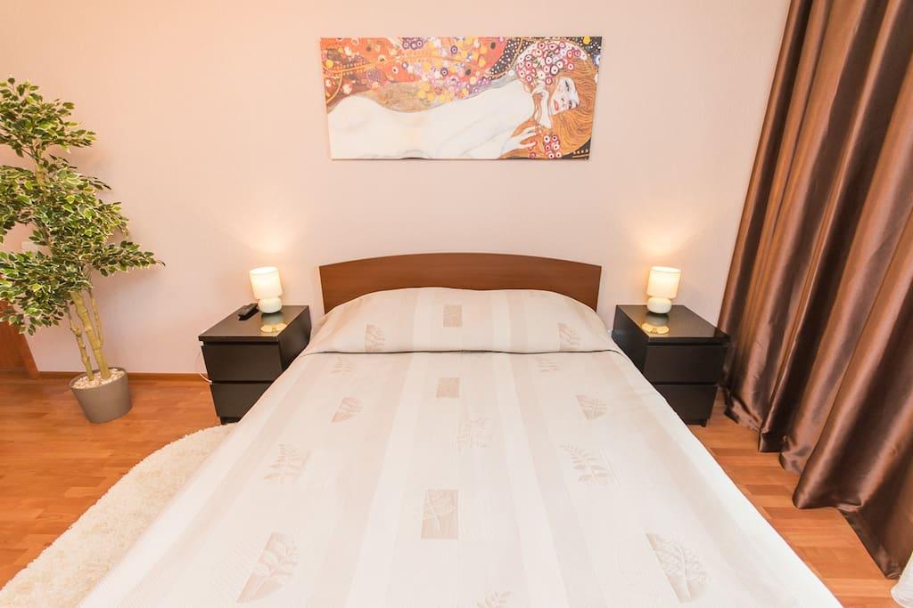 В спальной двуспальная кровать с заправленным чистым постельным бельем