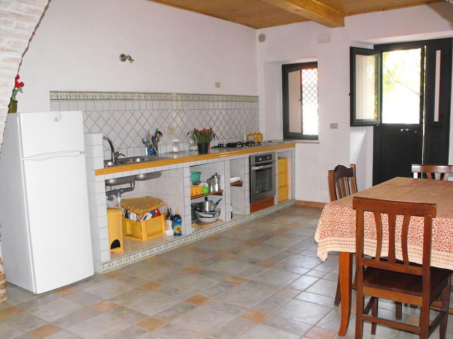 cucina in muratura con elettrodomestici e stoviglie