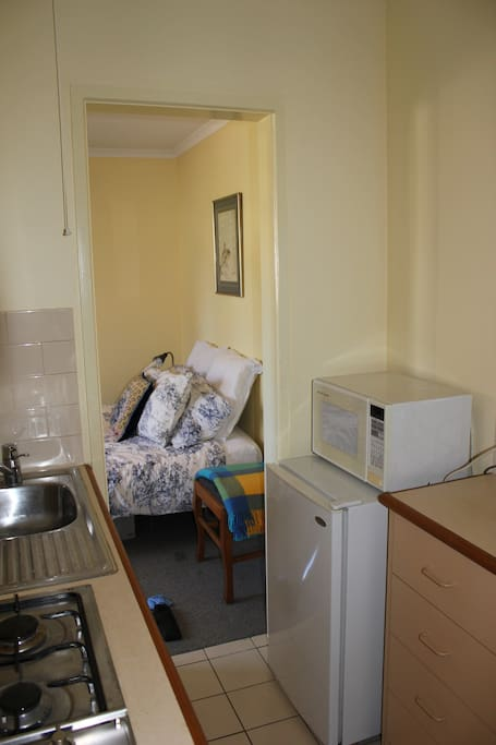 Galley kitchen fully equipped with fridge, microwave, gas cook top, kettle, crockery and cooking utensils.