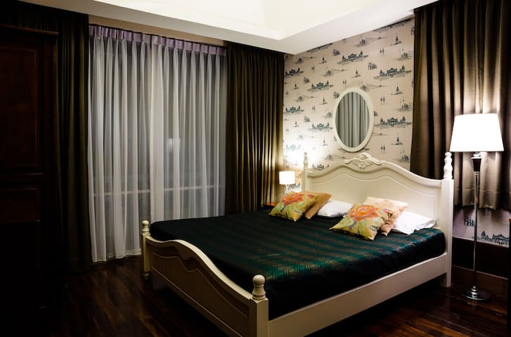 3rd Floor. Bedroom 7. Working room with Kingsize wooden bed, TV, Aircond, small balcony, office table and leather sofa. Night time