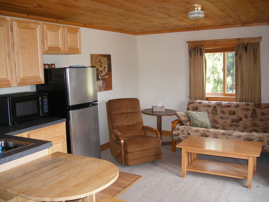 Cozy living room with futon that converts to bed for 2 additional guests, amenities kitchen, including 2 burner convection stove top, refrigerator and microwave, gas grill available during summer.