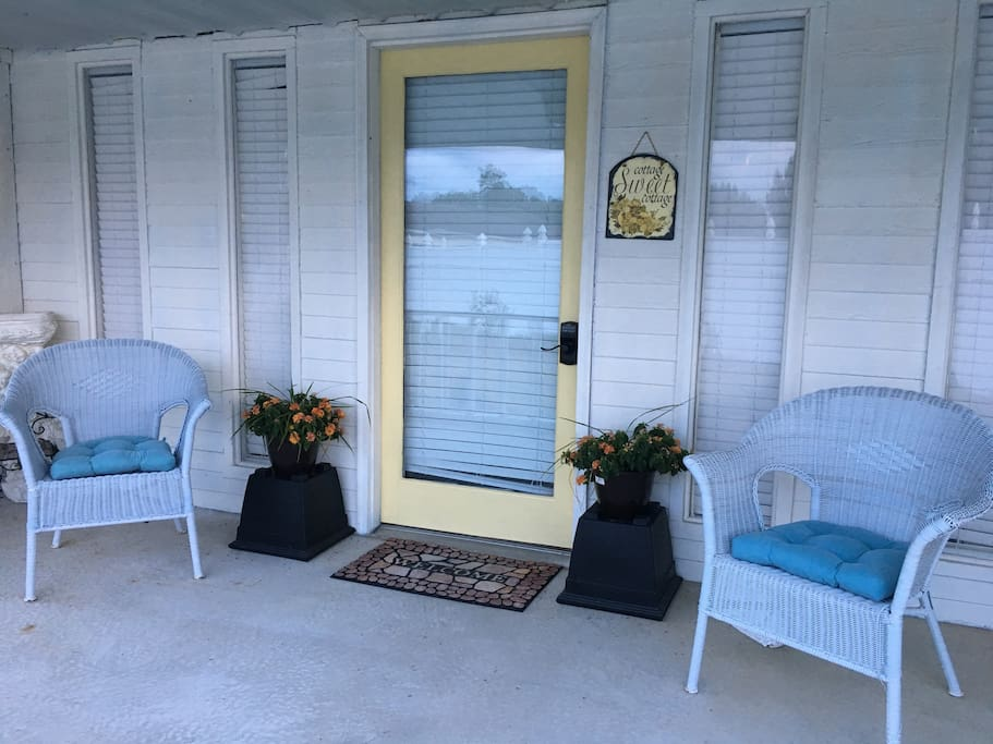WELCOME  HOME! The yellow door is your entrance to THE COTTAGE. This is a very cozy and comfortable place. Enjoy your private side porch and white fence enclosed backyard and view of the pond.