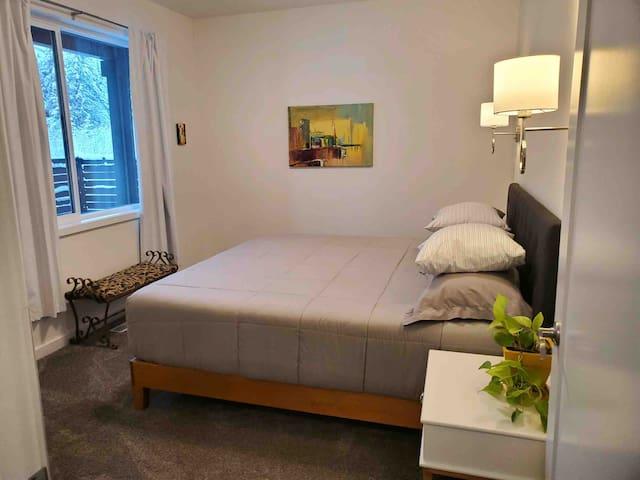 One bedroom includes a king size gel mattress with padded headboard, bedside reading lamps, and phone chargers.