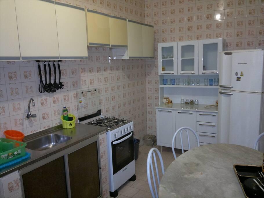 Cuisine avec frigo-congélateur, cuisinère-four et ustensiles (verres, assiettes, couteaux, fourchettes, cuillières, etc...).