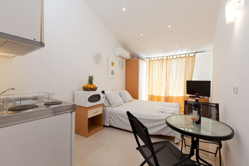 The studio has a small kitchen, double bed, satellite TV, AC, shower and toilet, and a balcony at the back
