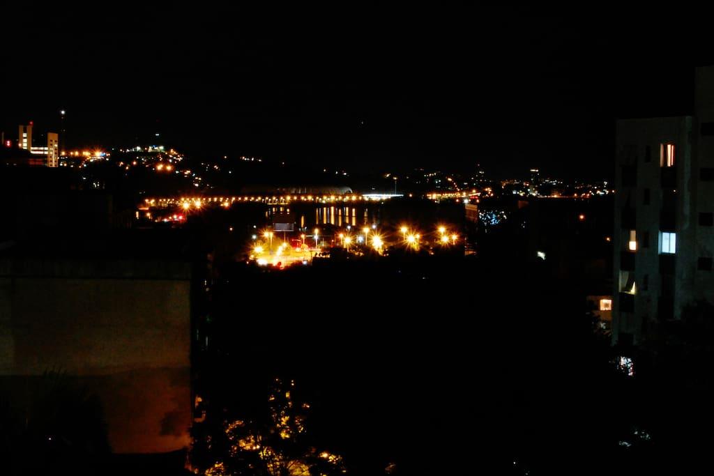 A noite, a orla do rio Guaíba iluminada.