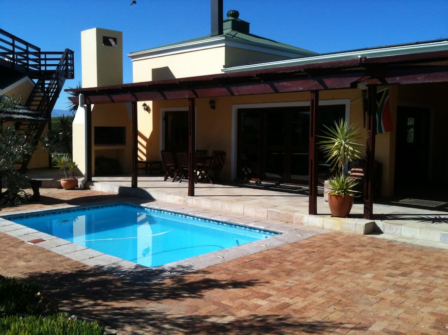 The villa is wrapped around a heated pool.