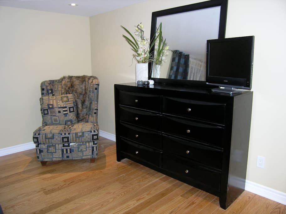 Master bedroom with TV, hard wood floors.