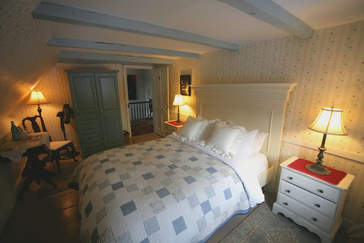 The Mistress and Maid room has a queen bed with a handmade quilt.