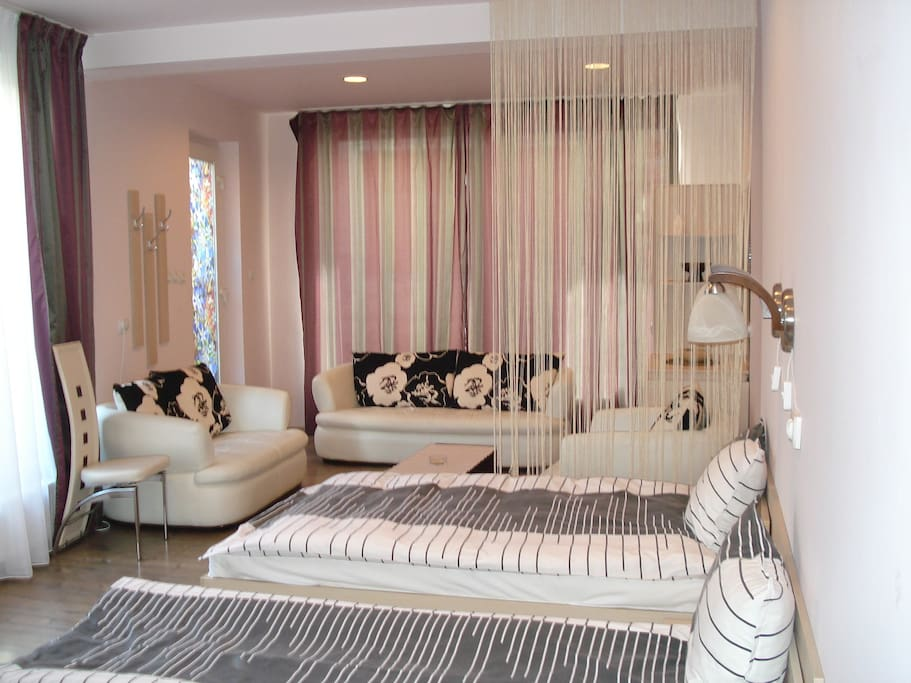 Two separate beds and  livingspace with white leather sofas