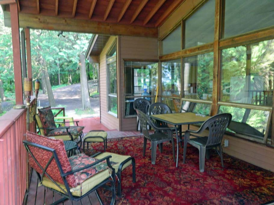 Covered deck with lots of lounge furniture and a propane BBQ